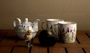 caeramic teapot and two cups against brown background