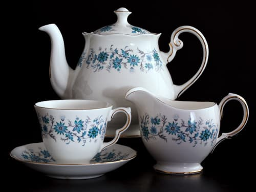 Teapot, cup and saucer against a black background