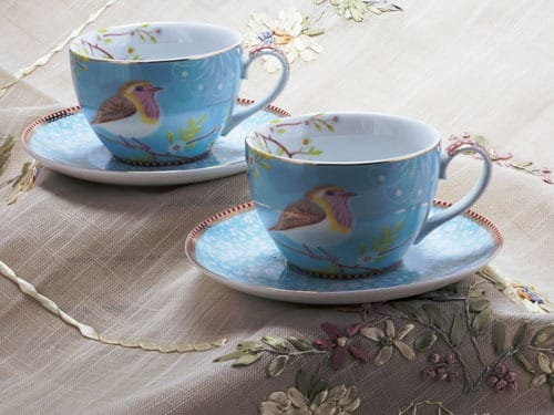 Two cups and saucers on a tablecloth