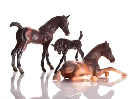 Product Photograph of three plastic horses in the sun