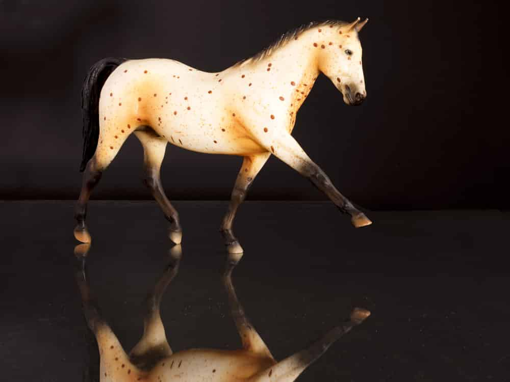 Product photograph of a plastic horse against a dark background